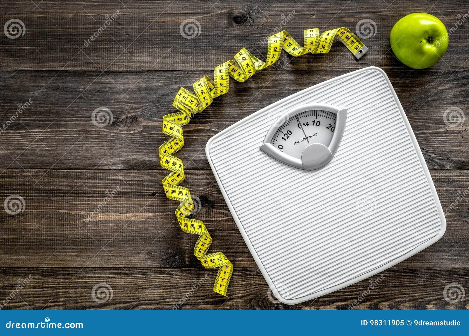 Perca o conceito do peso Escala de banheiro, fita de medição, maçãs no copyspace de madeira da opinião superior do fundo