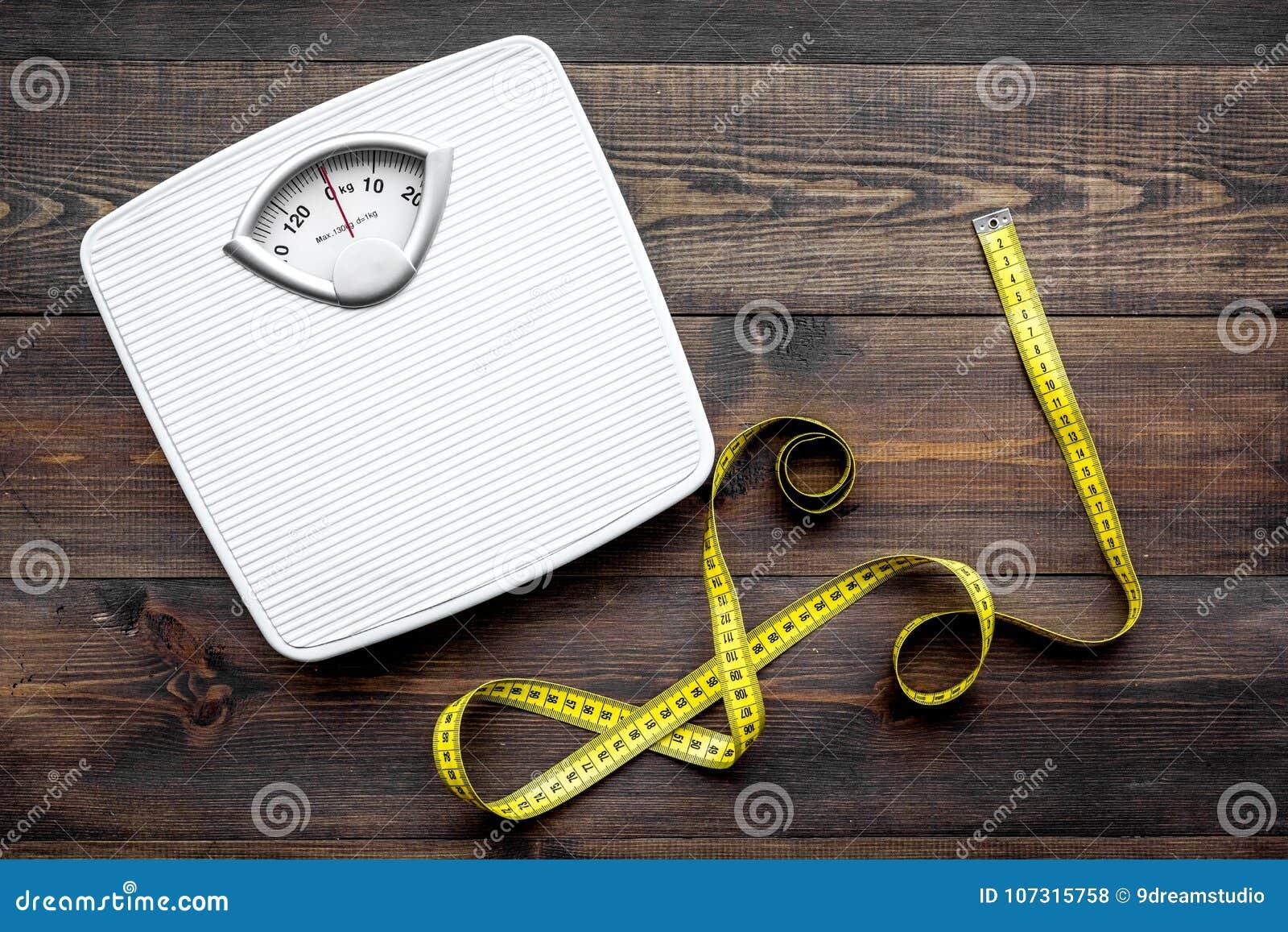 Perca o conceito do peso Escala e fita de medição na opinião superior do fundo de madeira escuro