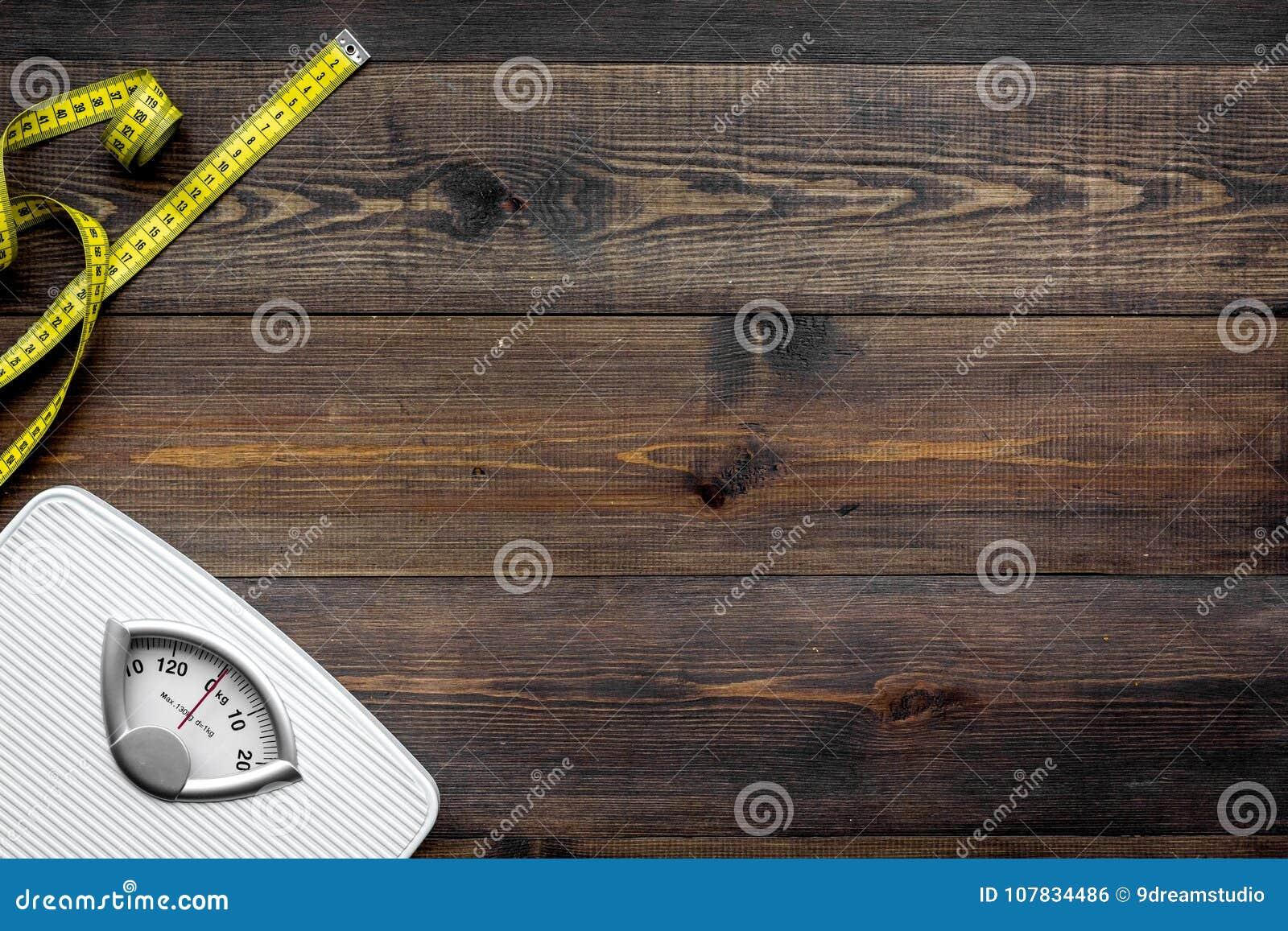 Perca o conceito do peso Escala e fita de medição no espaço de madeira escuro da cópia da opinião superior do fundo