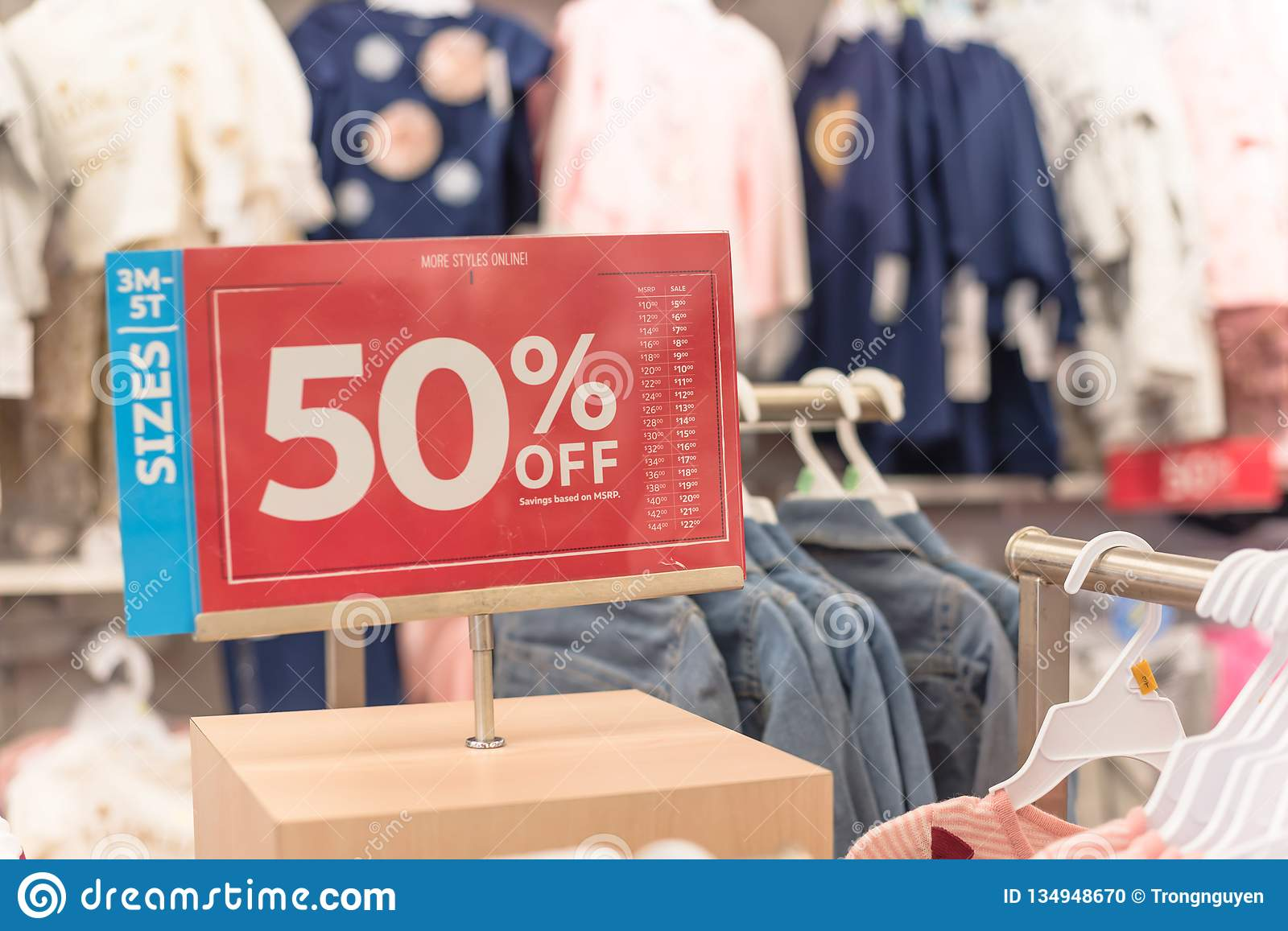 623686806 50 percent off sale sign over clothes at baby clothing store with customer  shopping