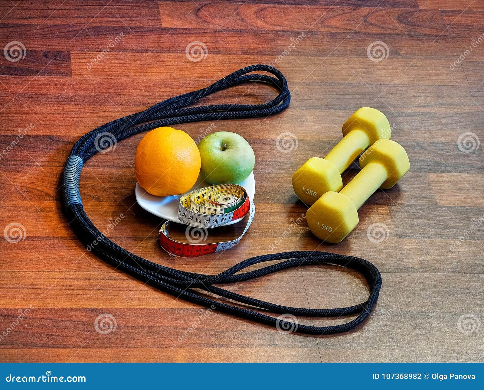 A perda de peso com o exercício e a dieta apropriada é os pesos, expansor, frutos, centímetro