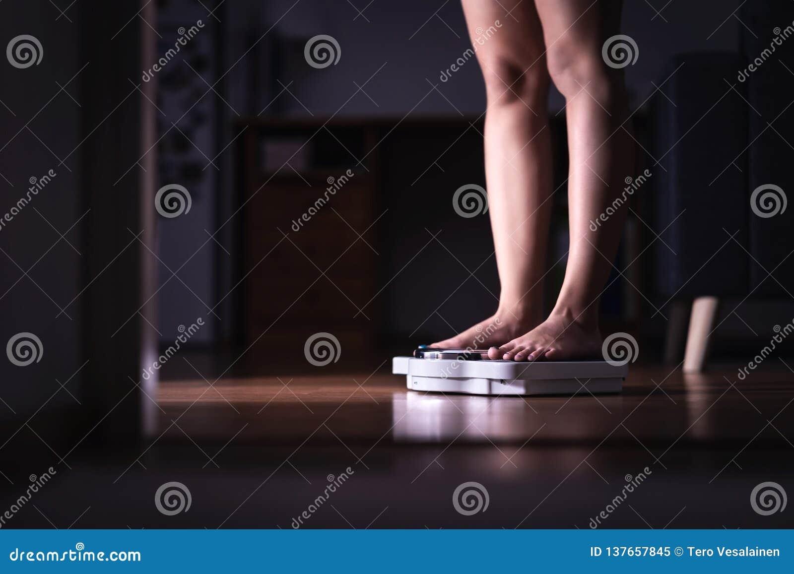 Perda de peso e conceito da dieta Senhora que está na escala Mulher que pesa-se Dieta da senhora da aptidão Weightloss e dietétic