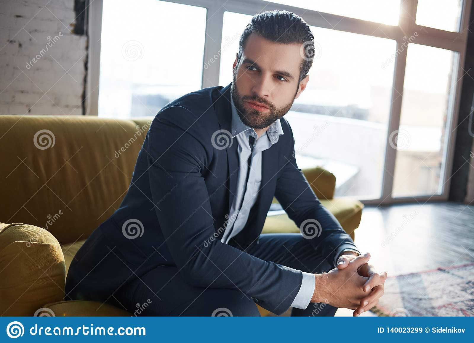 Perdido em pensamentos do negócio O homem de negócios novo considerável pensativo está pensando sobre o negócio ao sentar-se no s