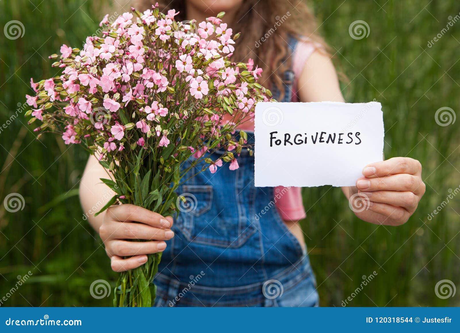 Perdono - donna con la parola ed il mazzo dei fiori rosa