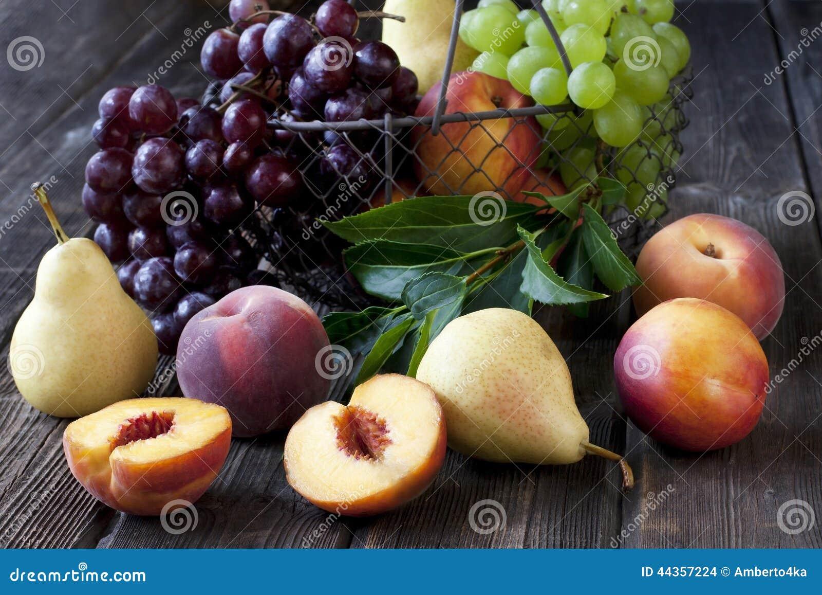 Pere, uva, nettarine e merce nel carrello saporite succose delle pesche