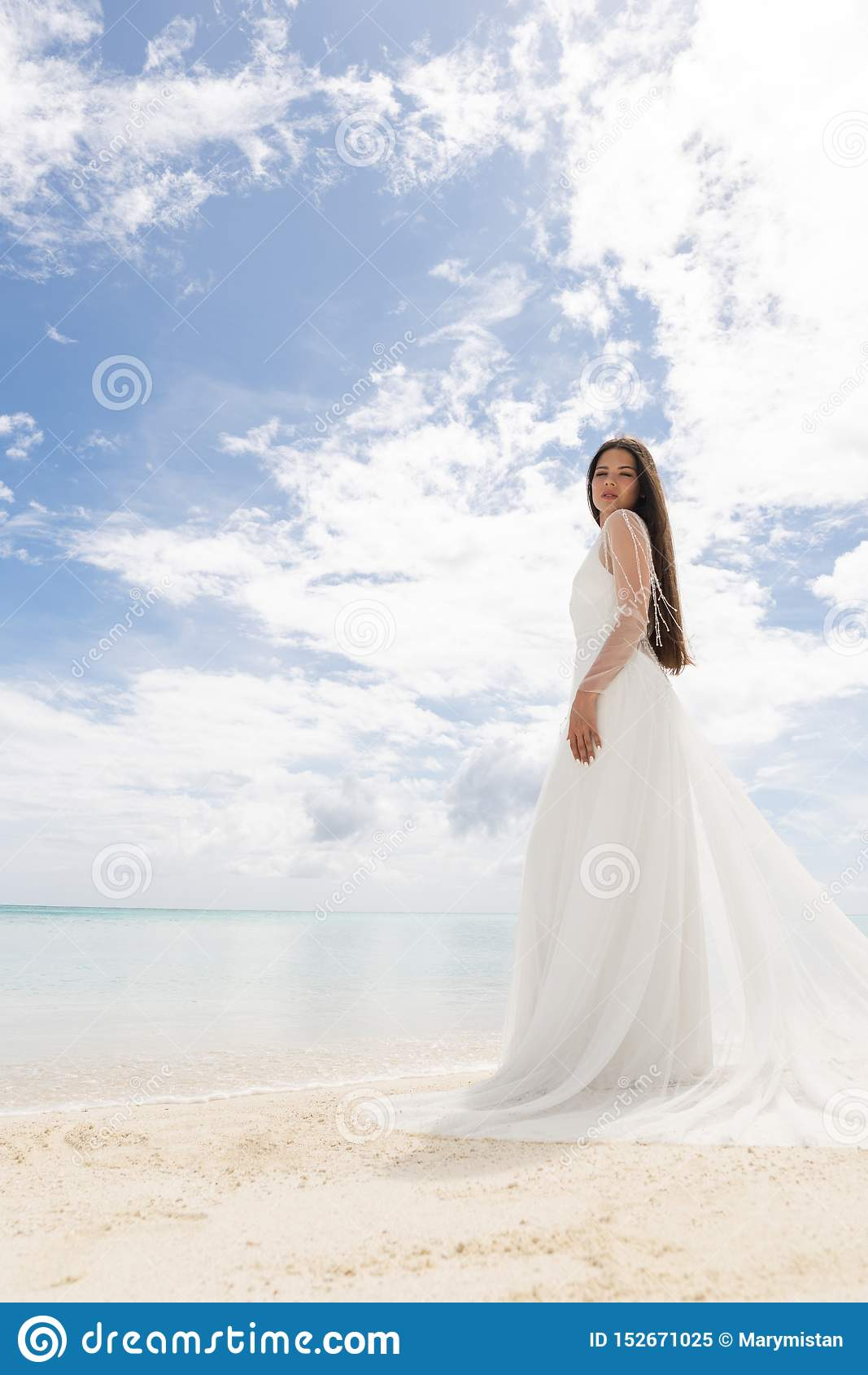 The perfect bride. A young bride in a white dress is standing on a snow-white beach