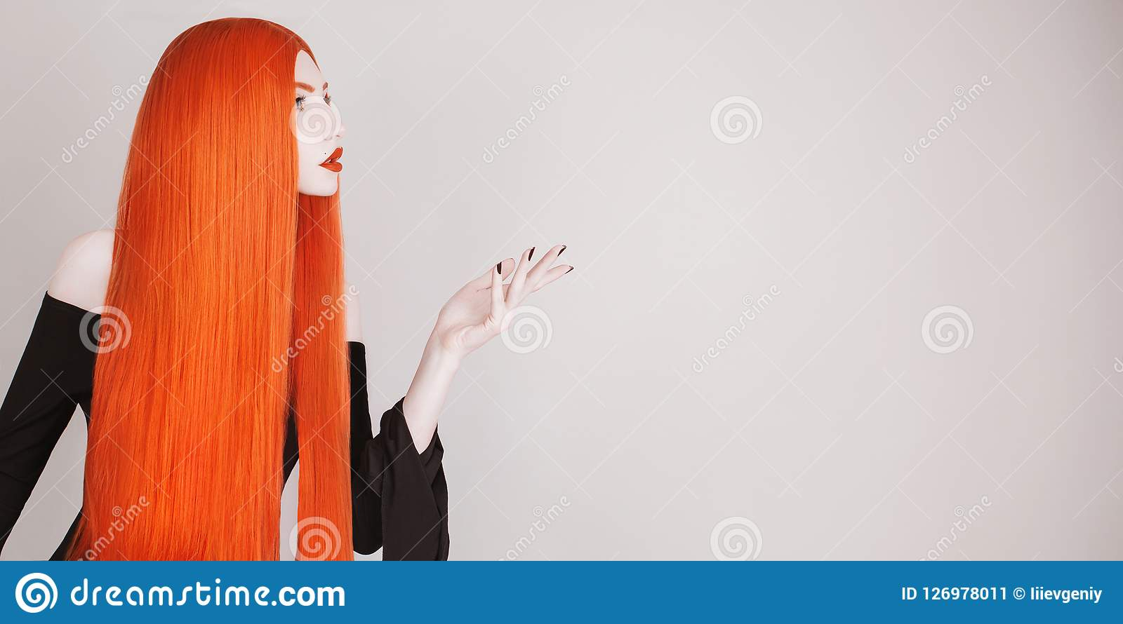 Perfect halloween attire. Gothic redhead woman with perfect straight hair in black dress advertise product. Redhead girl with red
