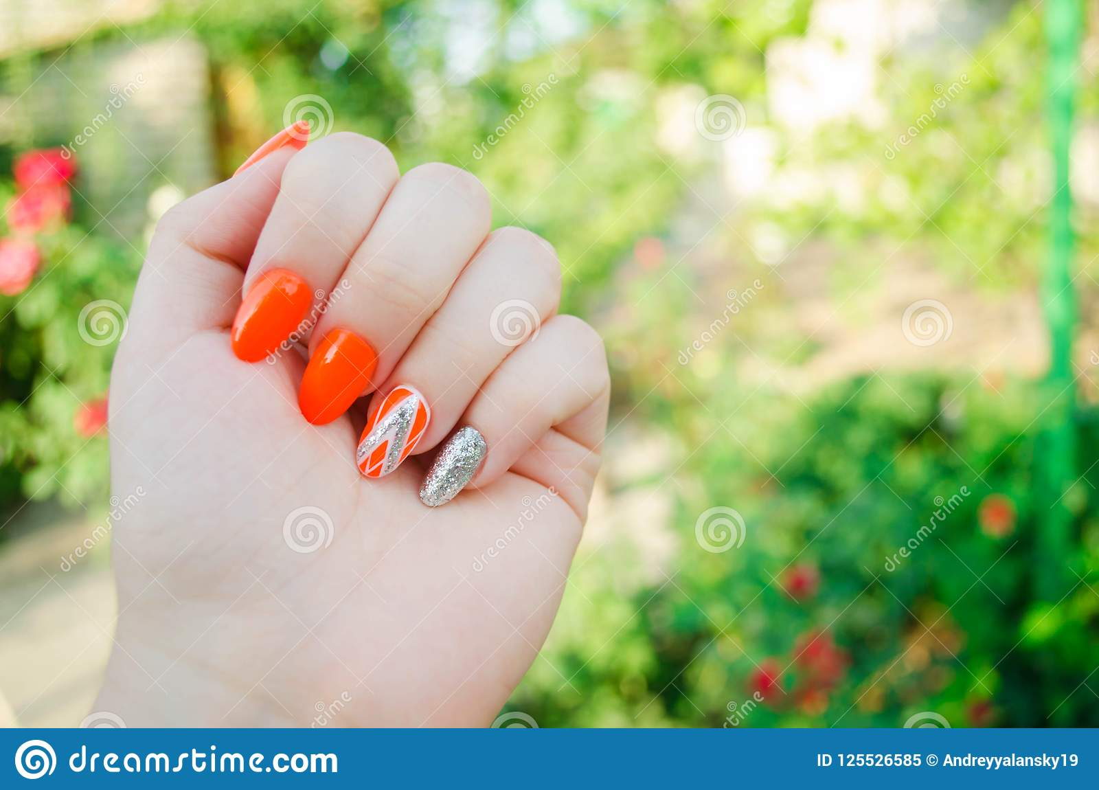 Perfect manicure and natural nails. Attractive modern nail art design. orange autumn design. long well-groomed nails