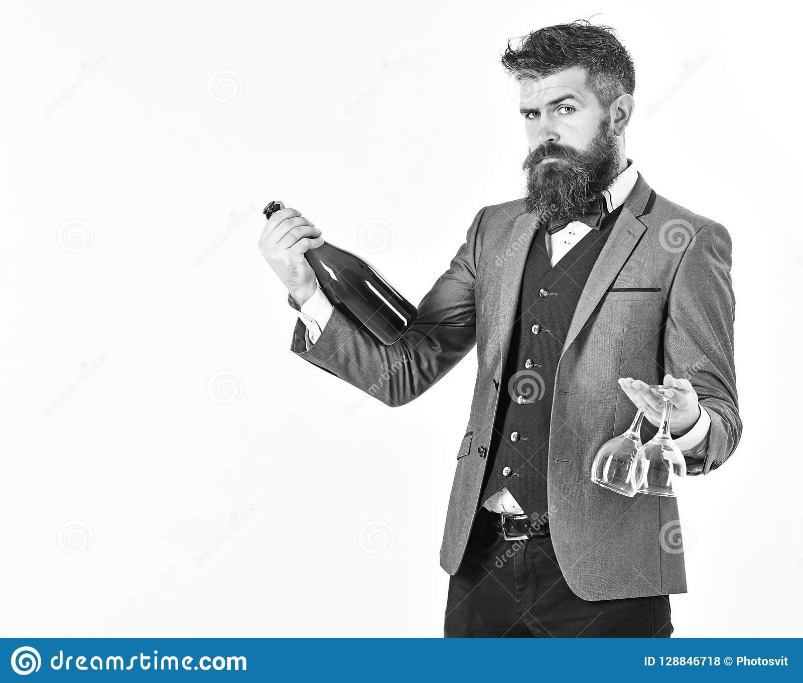 Perfect service, good manners, alcohol concept. Waiter with elegant suit, bow tie and handsome face. Mature man holds