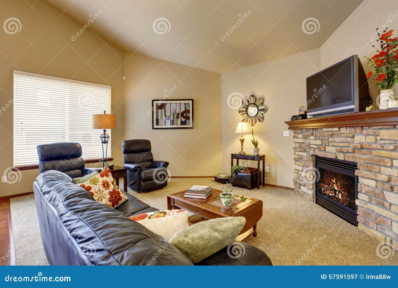Koraalkleur De Woonkamer : Perfecte woonkamer met leermeubilair en een open haard stock