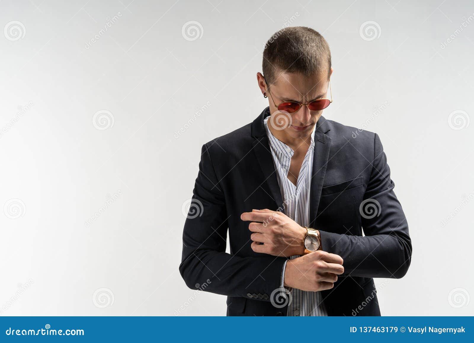 Perfectioneer aan het laatste detail Knappe jonge zakenman die zijn kokers aanpassen terwijl status tegen grijze achtergrond