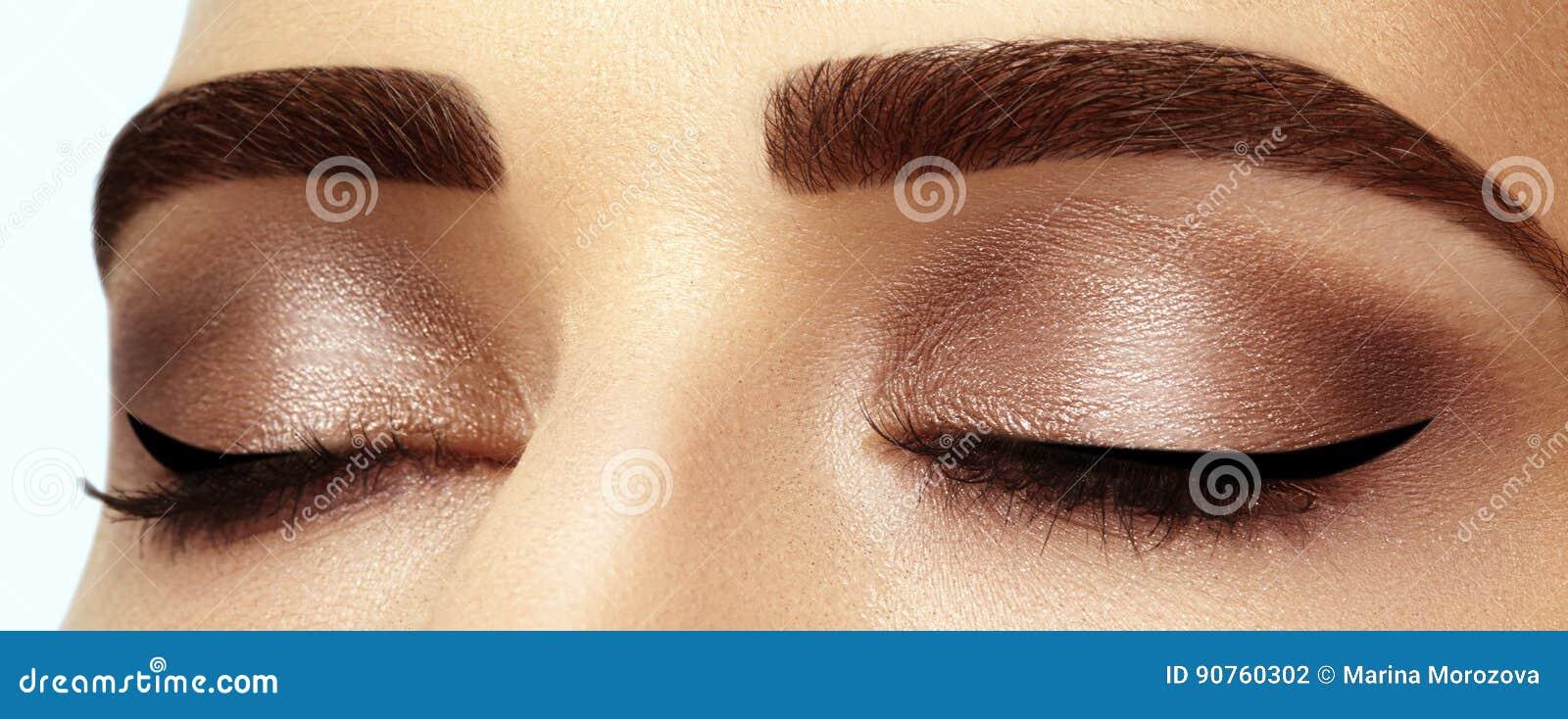 Perfekt form av ögonbryn, bruna ögonskuggor och långa ögonfrans Closeupmakroskott av rökig ögonanlete för mode