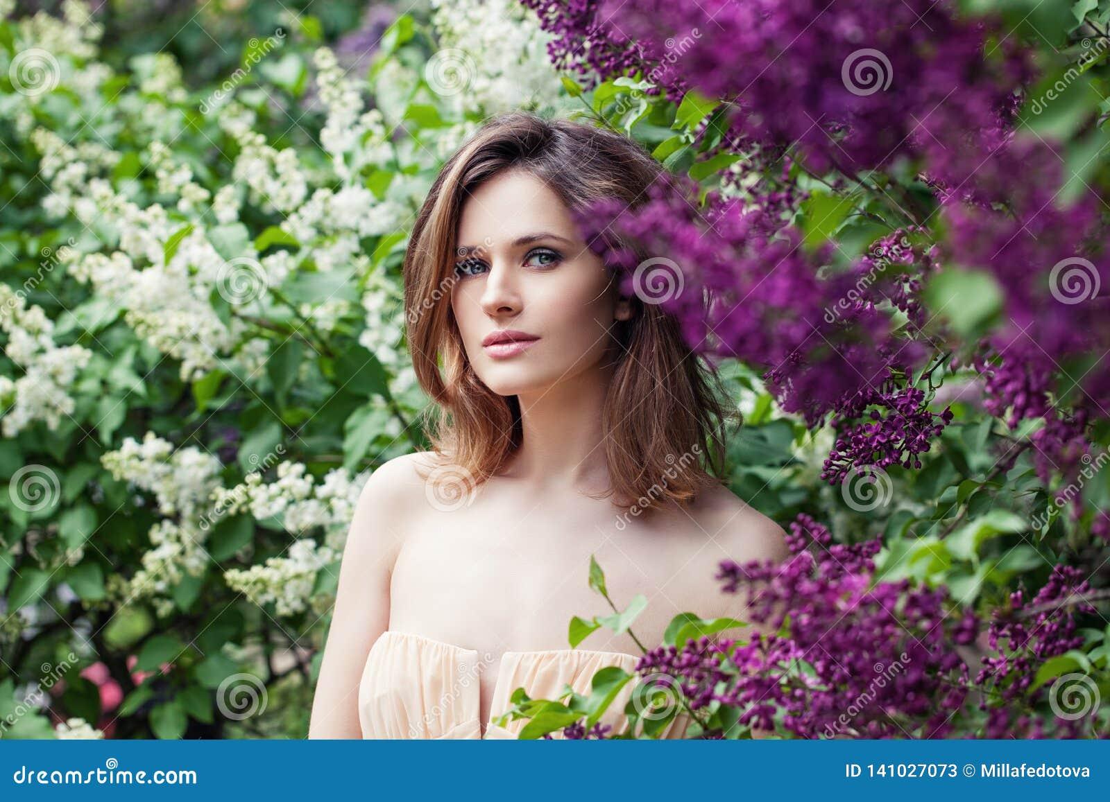 Perfekt kvinnlig framsida i lila blommaträdgård Nätt kvinna på blom- bakgrund
