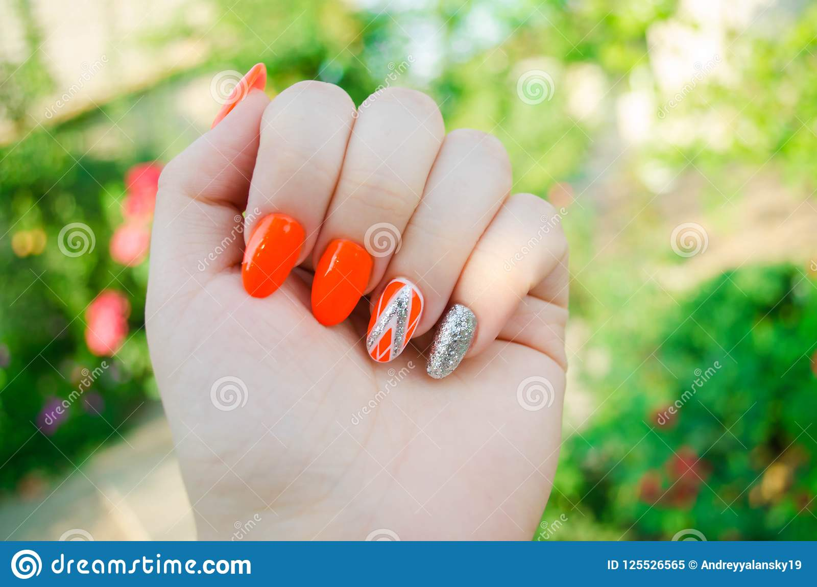 Perfekte Maniküre und natürliche Nägel Attraktives modernes Nagelkunstdesign orange Herbstdesign lange gut-gepflegte Nägel