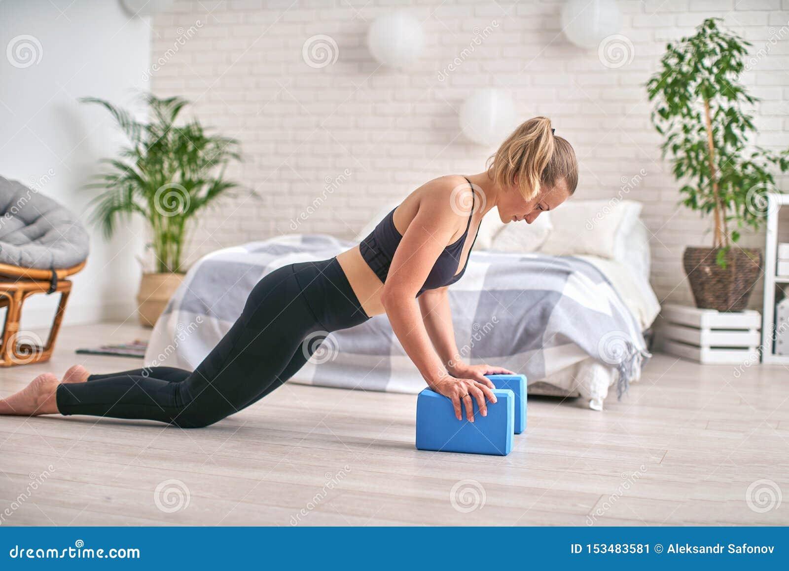 Perfil da vista lateral do atleta bem-dado forma Est? ficando na prancha e est? usando blocos da ioga para os pulsos