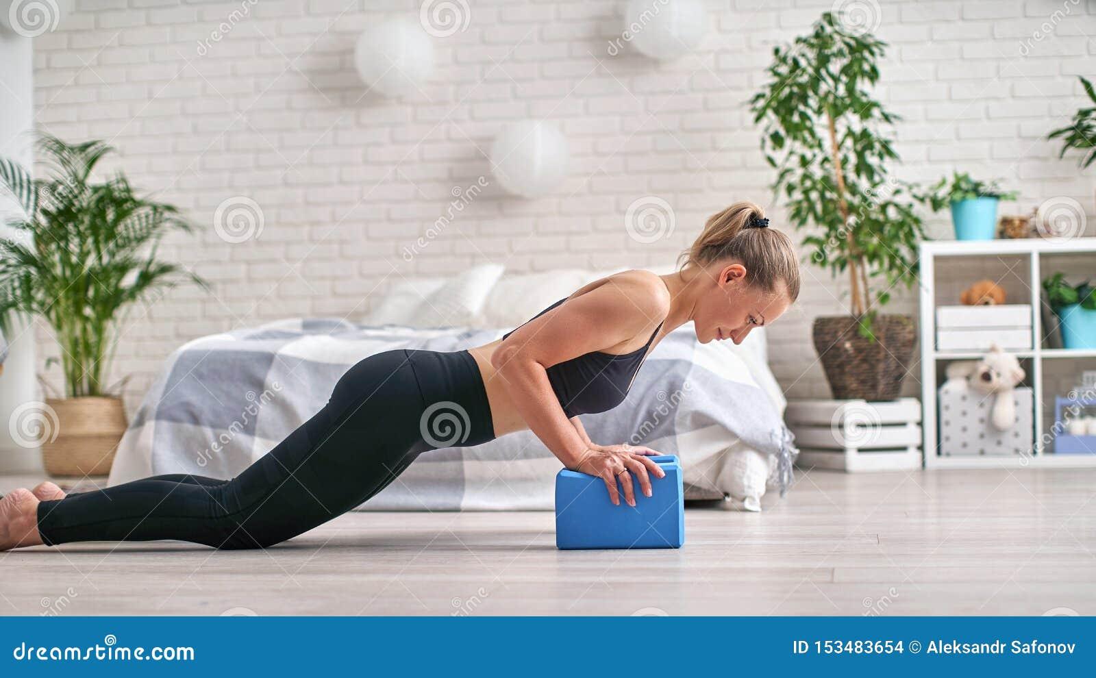 Perfil de la vista lateral del atleta bien formado Ella est? permaneciendo en tabl?n y est? utilizando los bloques de la yoga par