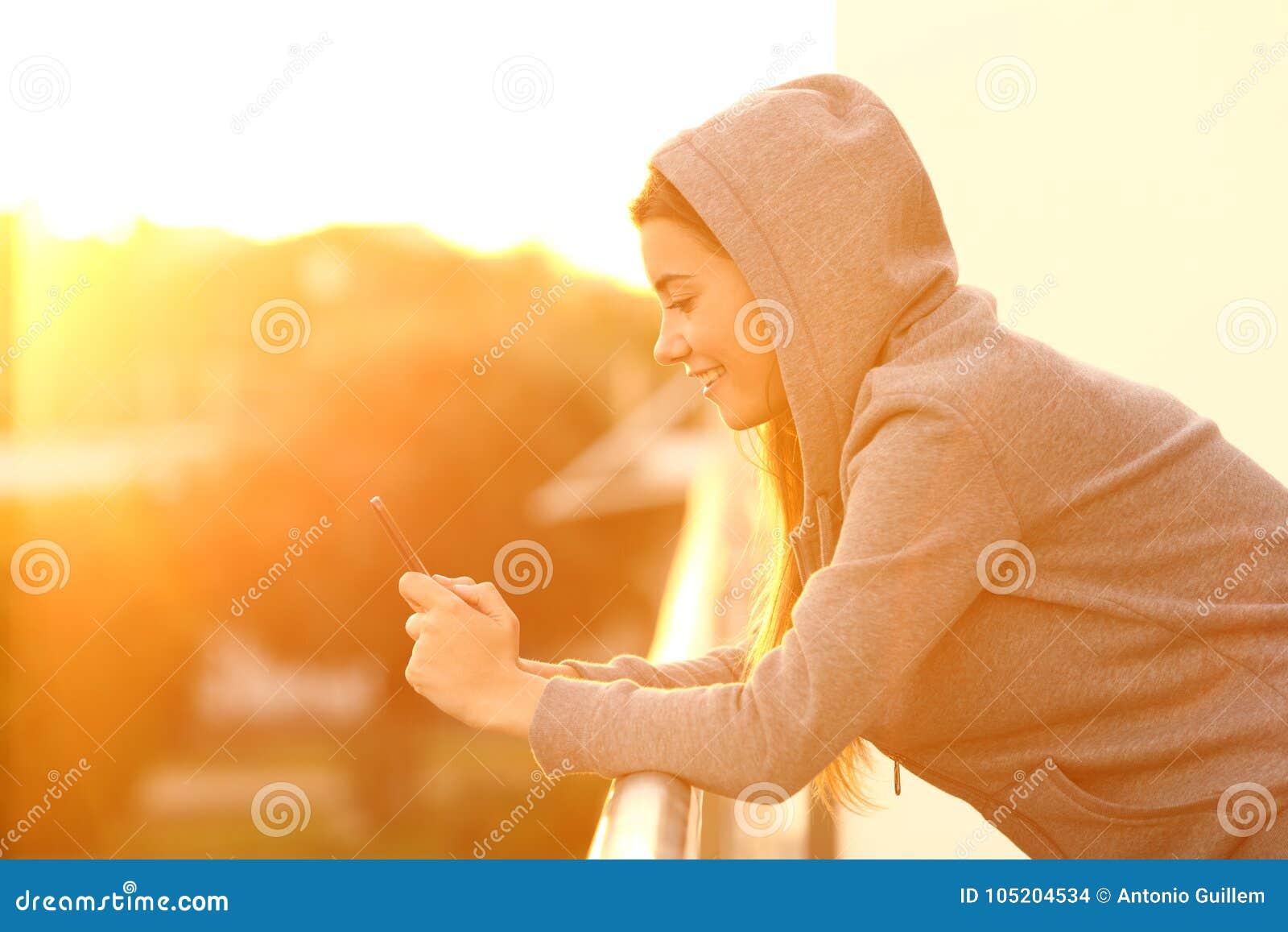 Perfil de um adolescente usando um telefone esperto em um balcão