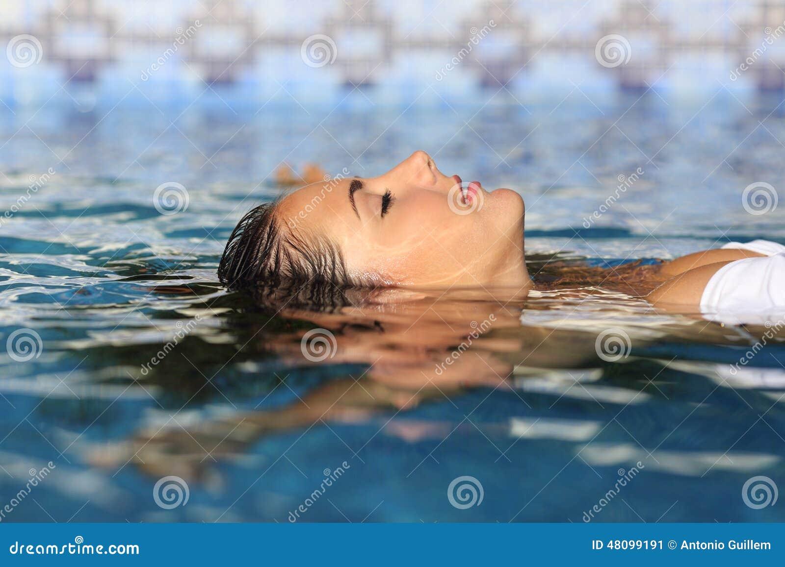 Perfil de uma cara relaxado da mulher da beleza que flutua na água