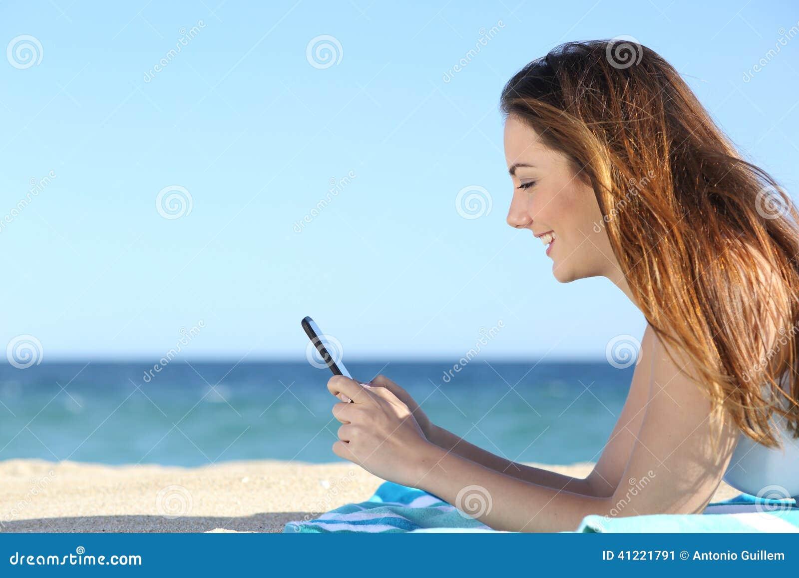 Perfil de uma mulher que texting em um telefone esperto na praia