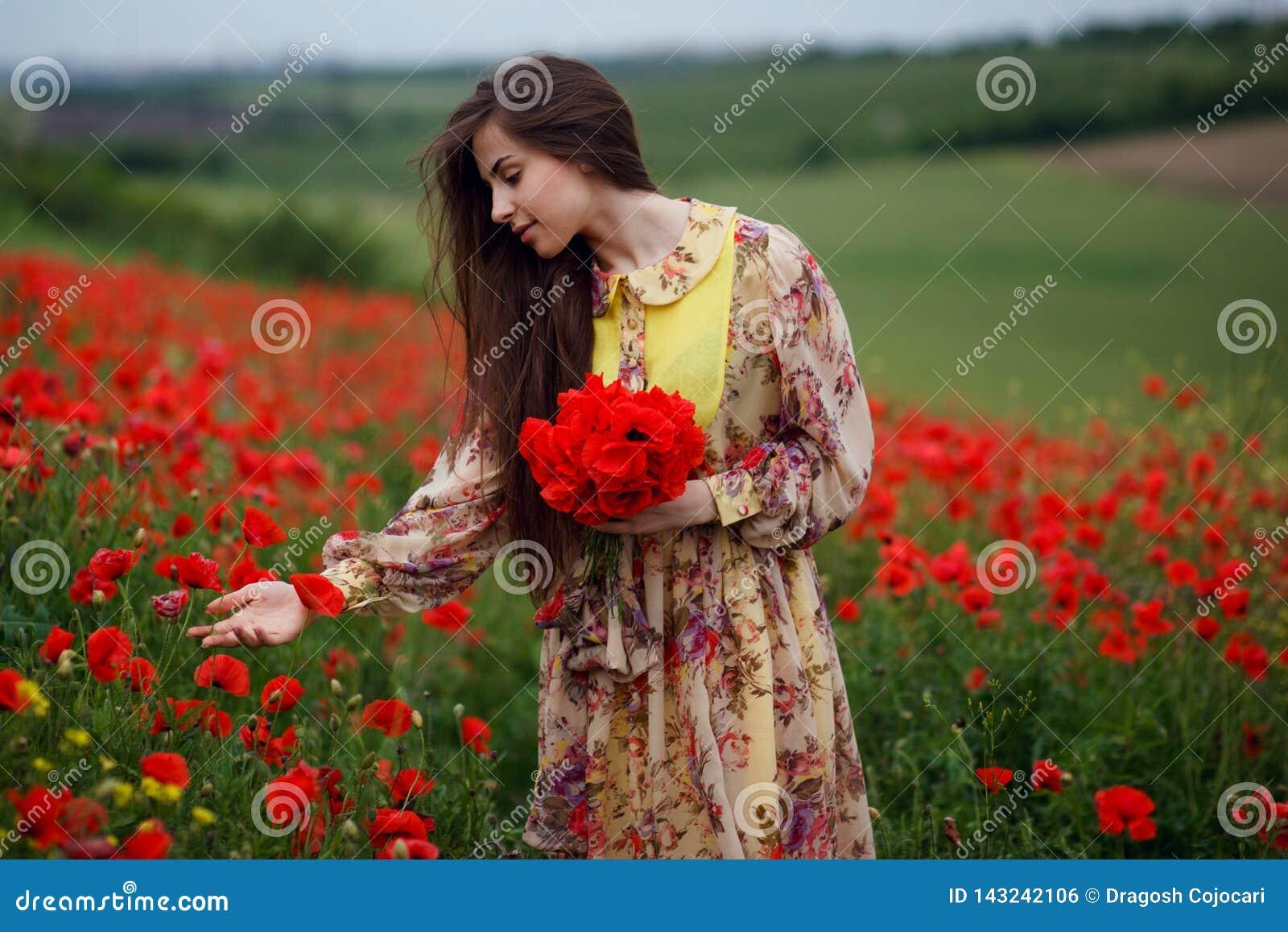 Perfil de una mujer joven hermosa, pelo largo, colocándose en el campo de flor rojo de la amapola, fondo hermoso del paisaje