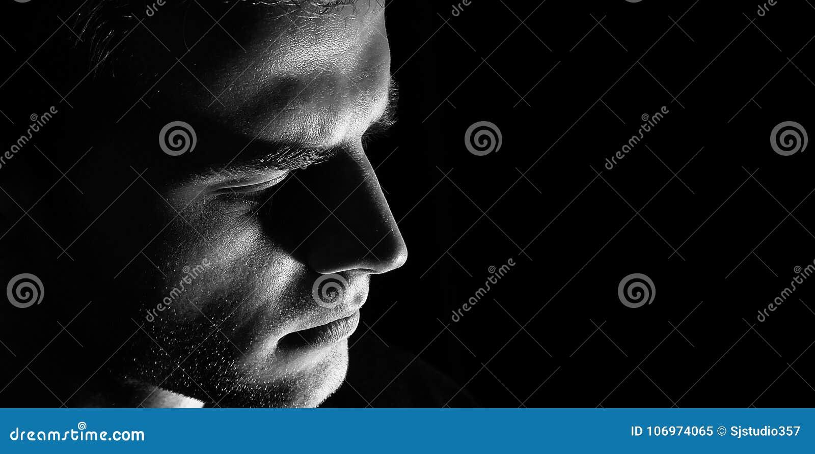 Perfil triste do homem, homem escuro do indivíduo na depressão, olhar preto e branco, sério