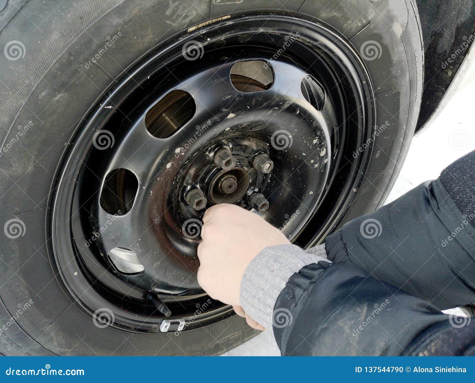 Perforado y neumático desinflado en el camino Reemplazo de la rueda por un enchufe por el conductor