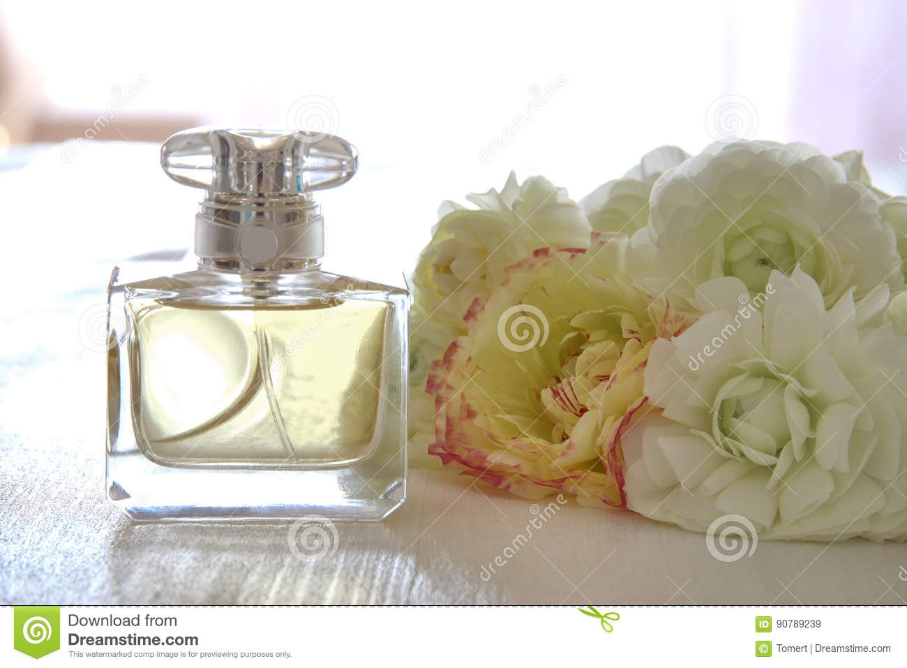 Perfume Bottle Next To Aromatic Flowers On White Table Stock Image