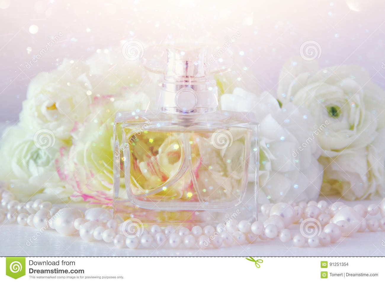 Perfume Bottle And Pearls Necklace Next To Aromatic Flowers Stock