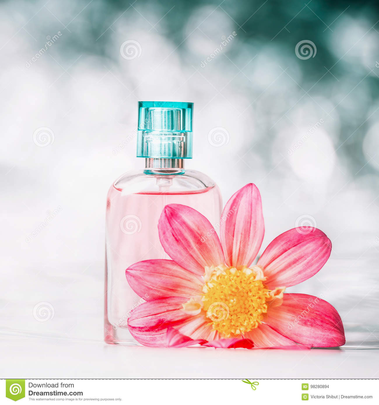 Perfume Bottle With Pink Flower At Bokeh Background Front View