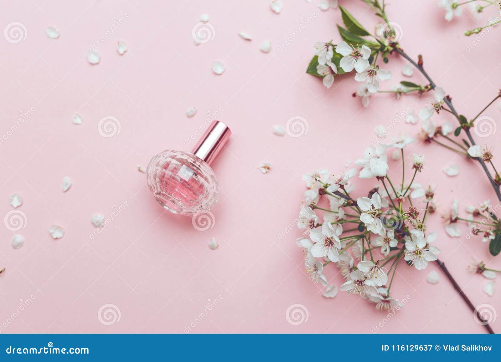 Perfume do pulverizador da mão do ` s das mulheres arranjo de flor Flores, fragrância, perfume no fundo cor-de-rosa