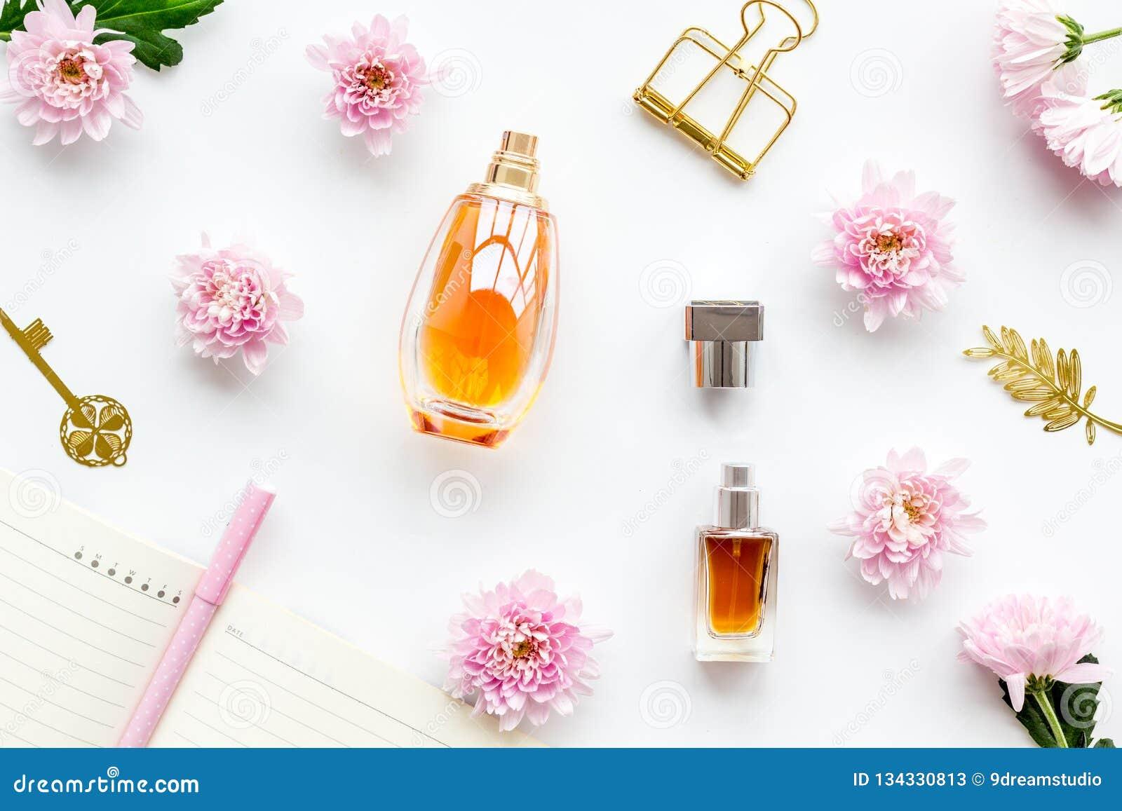d7955e500365 Mesa feminino Acessórios do ` s das mulheres Perfume perto do caderno para  a leiteria entre flores na opinião superior do fundo branco