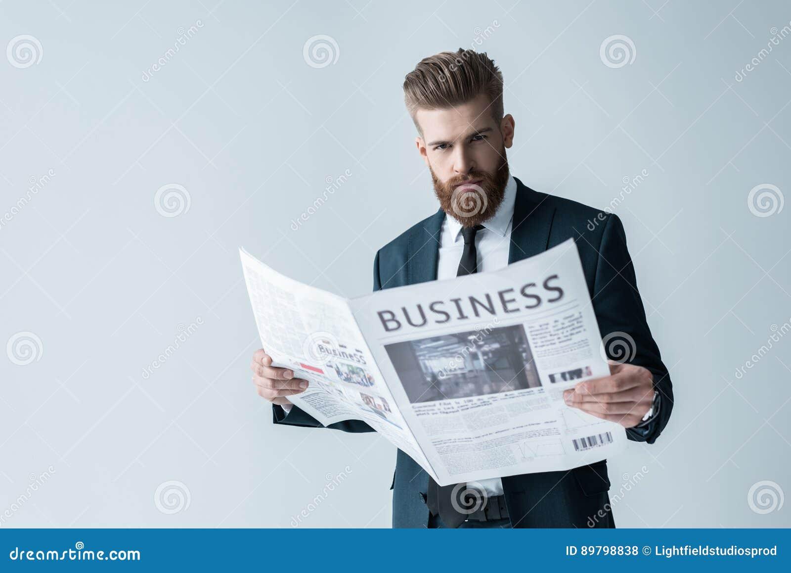 Periódico barbudo de la lectura del hombre de negocios en gris