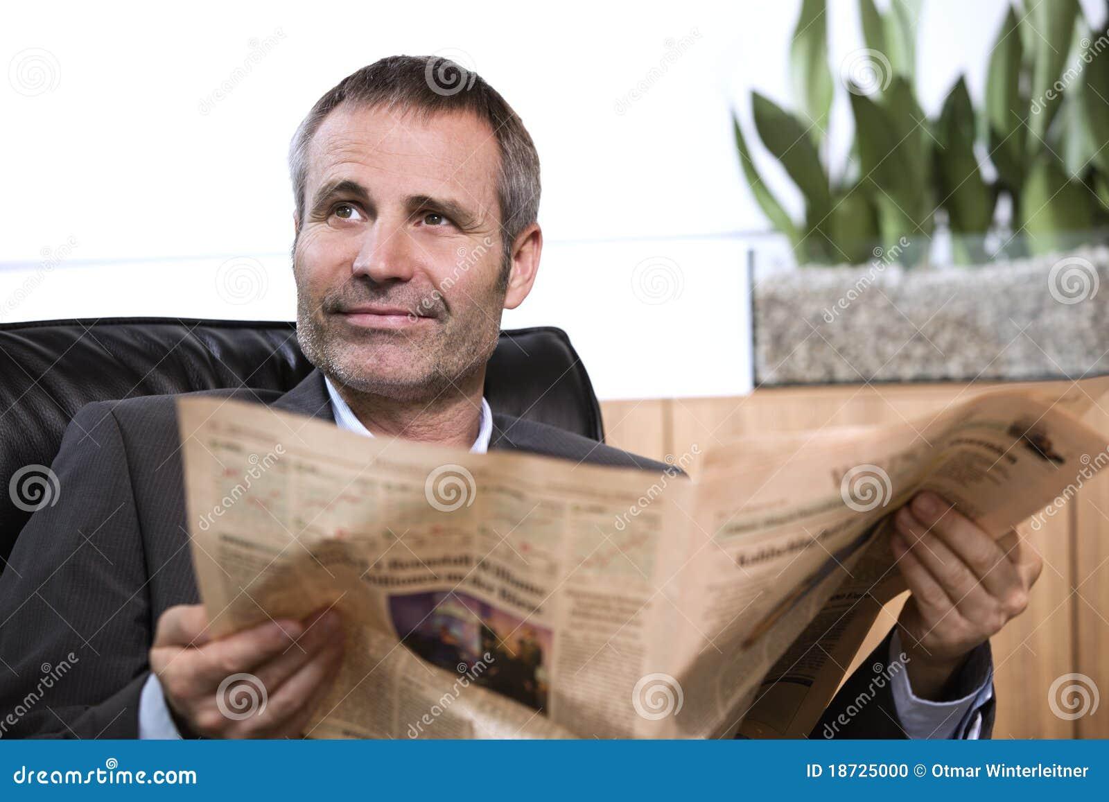 Periódico de la lectura del hombre de negocios y mirada para arriba.