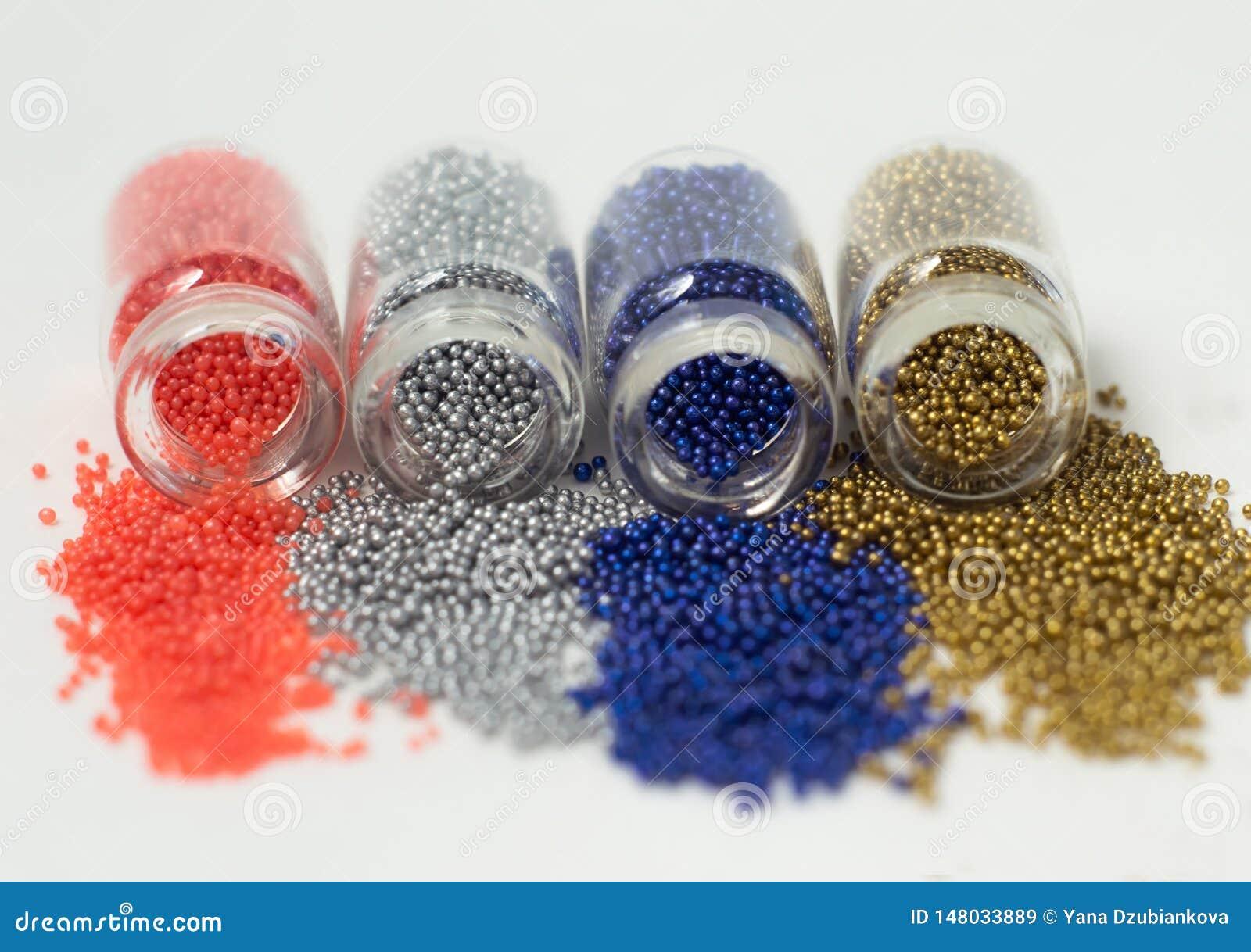 Perle multicolori in barattoli di vetro Le perle sono versate su un fondo bianco Di polimeri colorati multi di plastica Pillets d