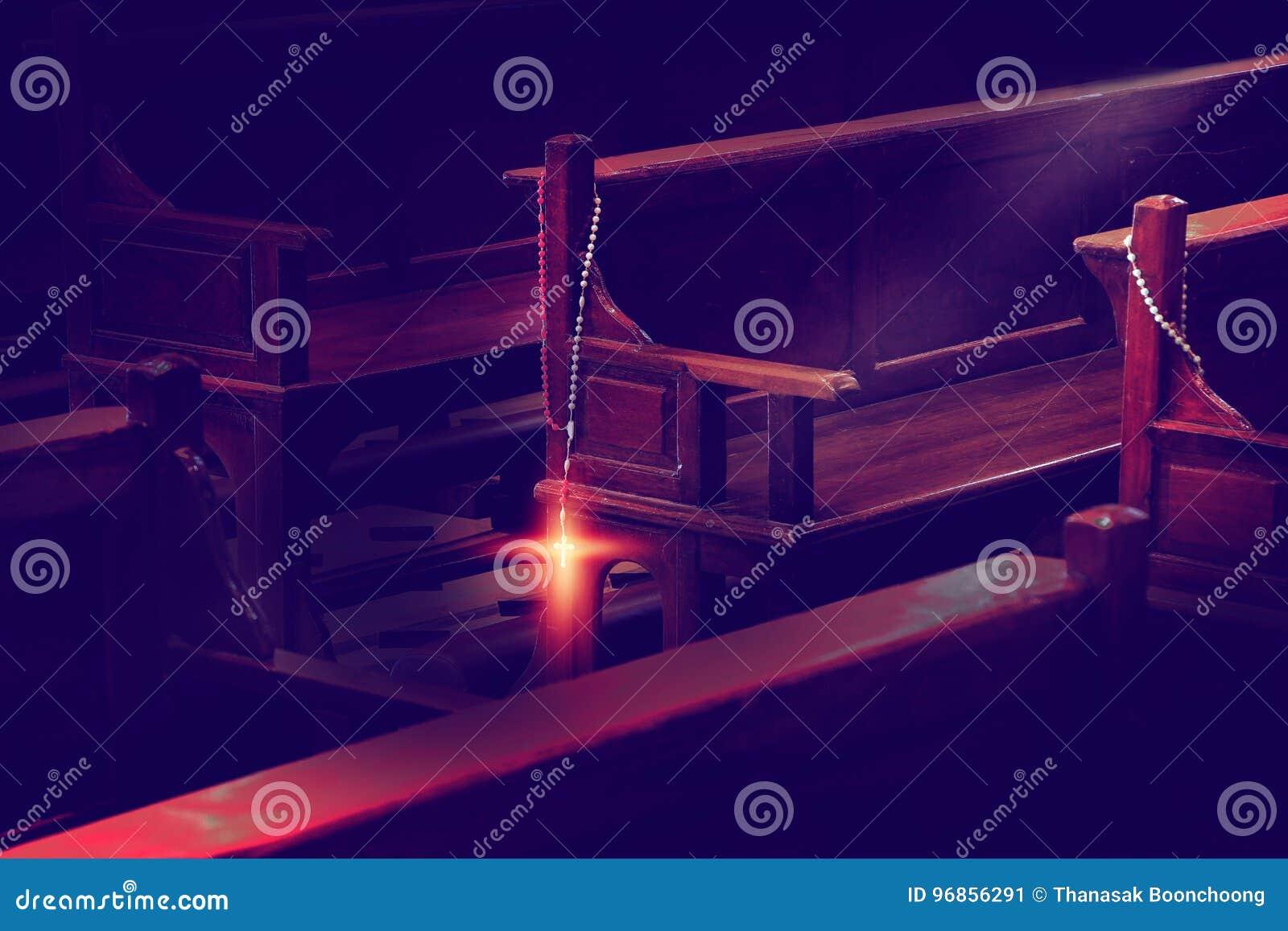 Perles de chapelet accrochant sur les bancs en bois d église