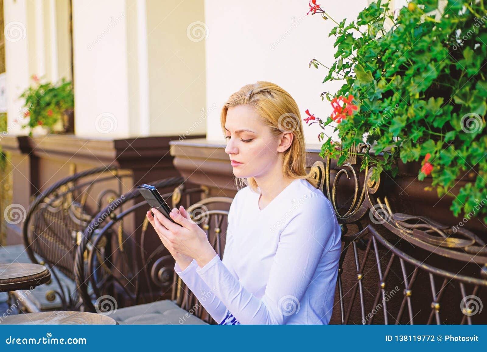 Permaneça em contacto Fundo urbano texting do terraço do café do smartphone da cara calma da mulher O branco texting do amigo da