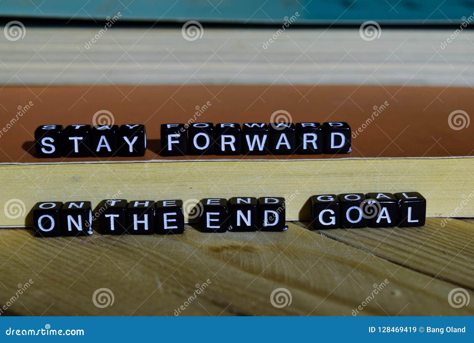 Permanezca delantero en el objetivo final en bloques de madera Concepto de la motivación y de la inspiración