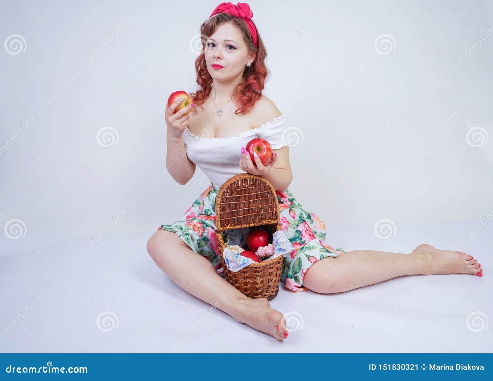 Perno grazioso sulla posa felice della ragazza caucasica con le mele rosse signora d annata sveglia in retro vestito divertendosi