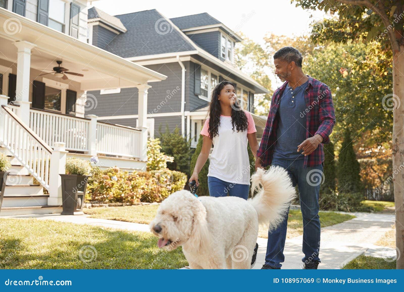 Perro de And Daughter Walking del padre a lo largo de la calle suburbana