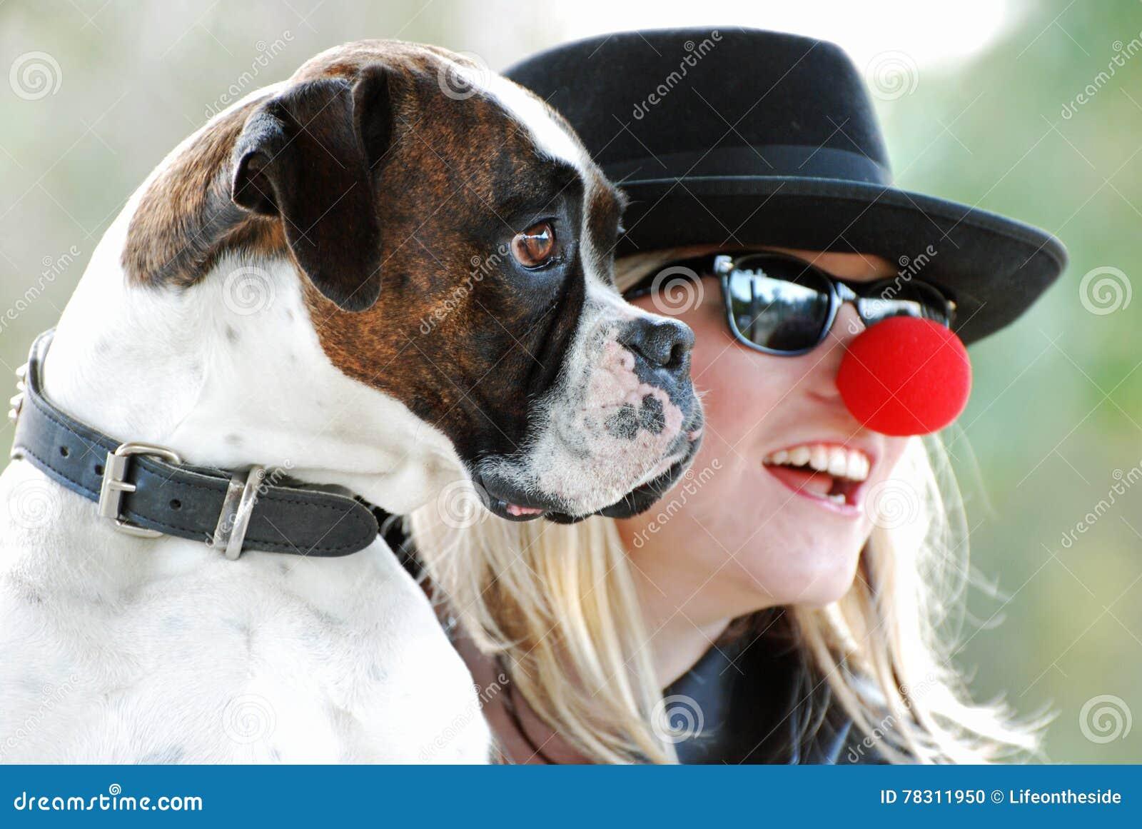 Perro del boxeador que presenta para la fotografía con el dueño feliz de la mujer bastante joven