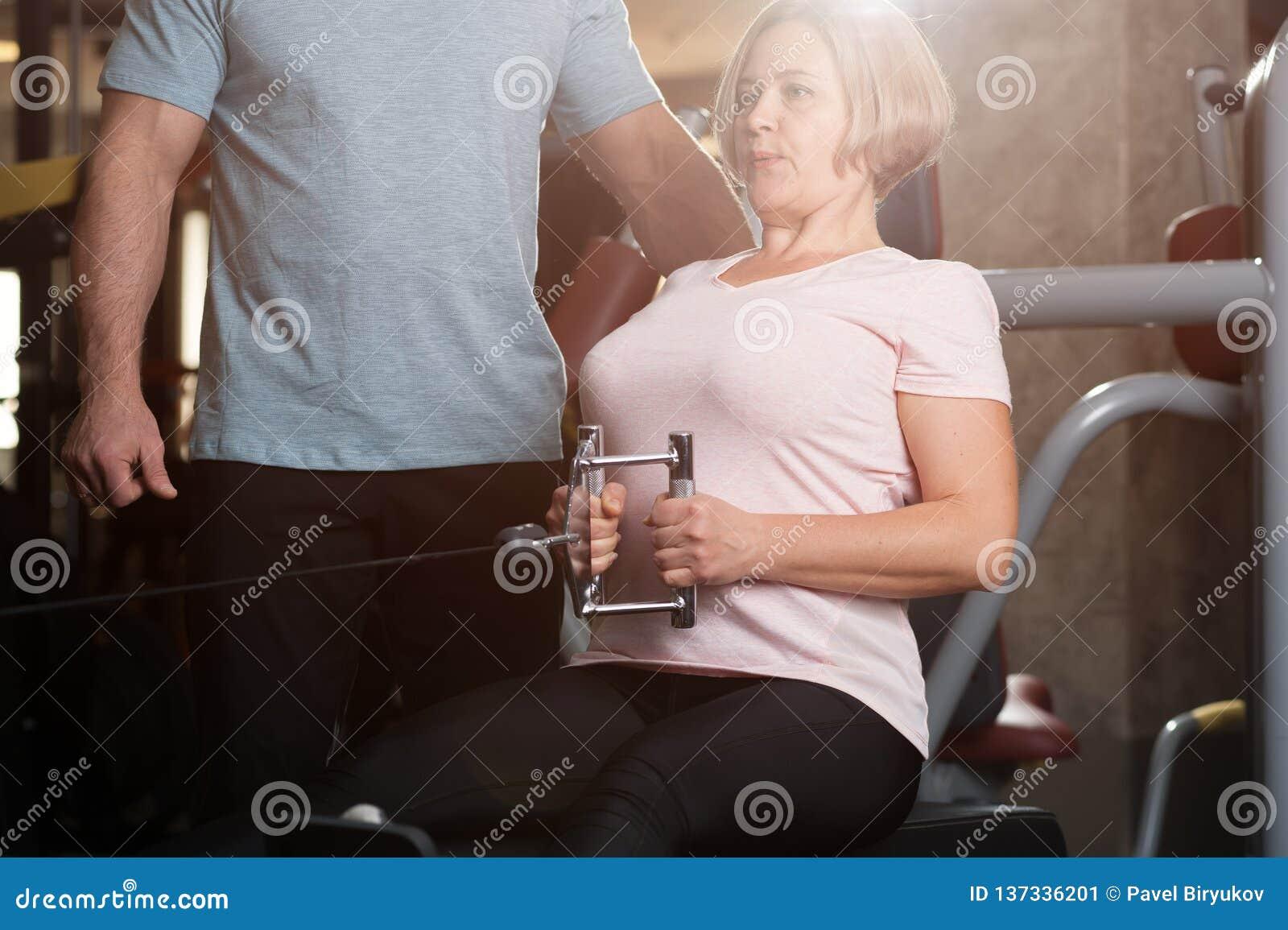 Persönlicher Trainermann hilft einer älteren Frau