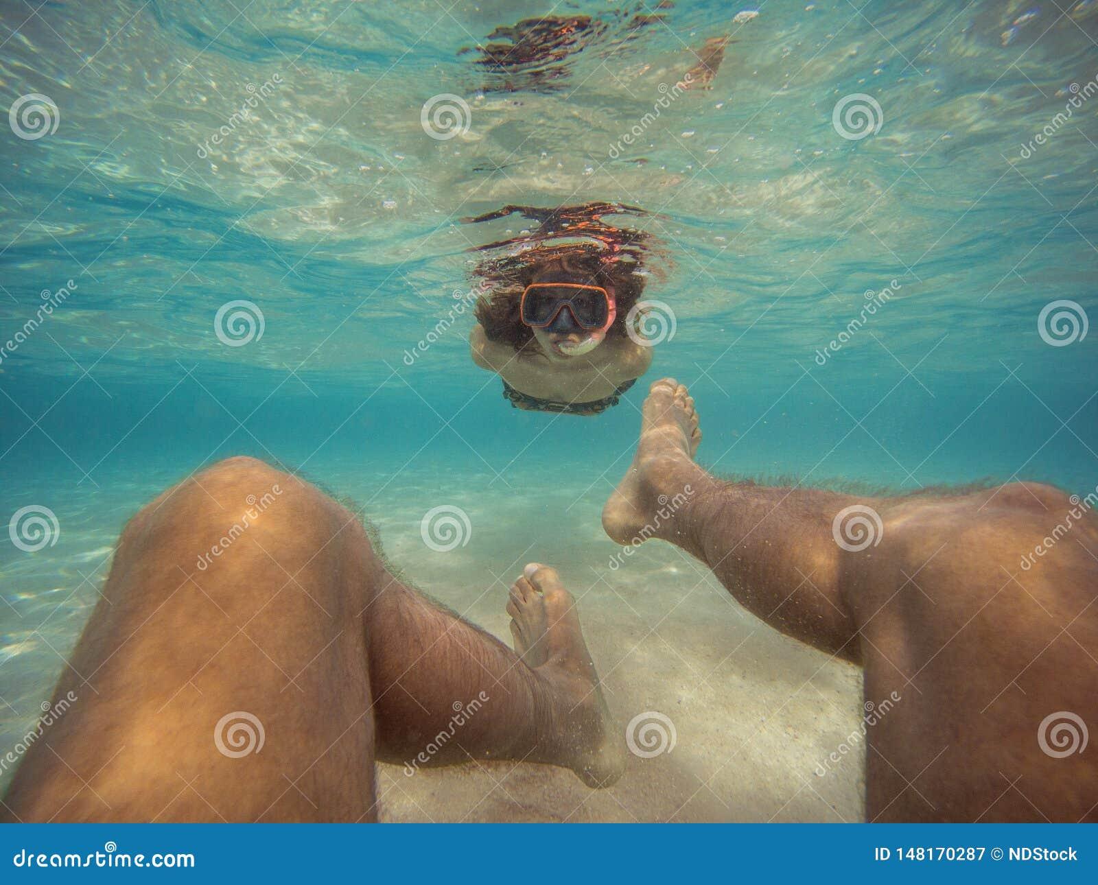 Pers?nliche Perspektive einer m?nnlichen Schwimmens r?ckw?rts Unterwasser Junge Frau, die ihrem Freund folgt