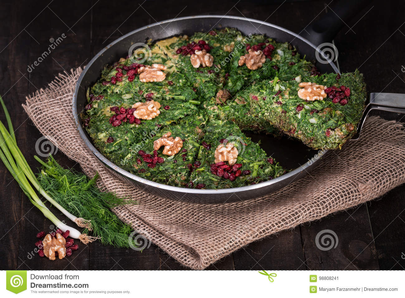 Persian Mixed herbs frittata with barberry and walnut in pan Kuku and Zereshk