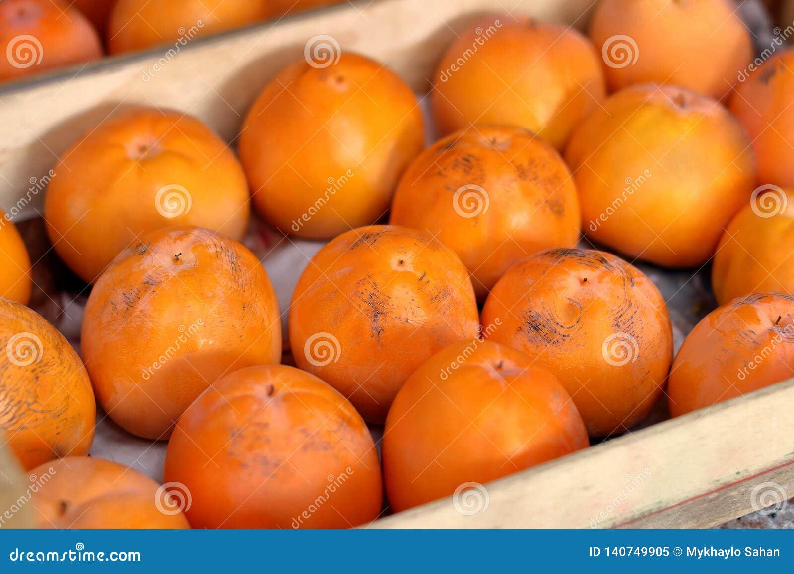 Persimonfrukt i träasken