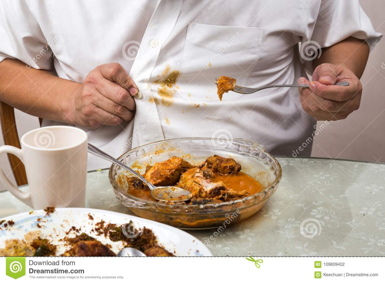 Person Accidently Spilled Curry Stain Onto White Shirt Stock Photo