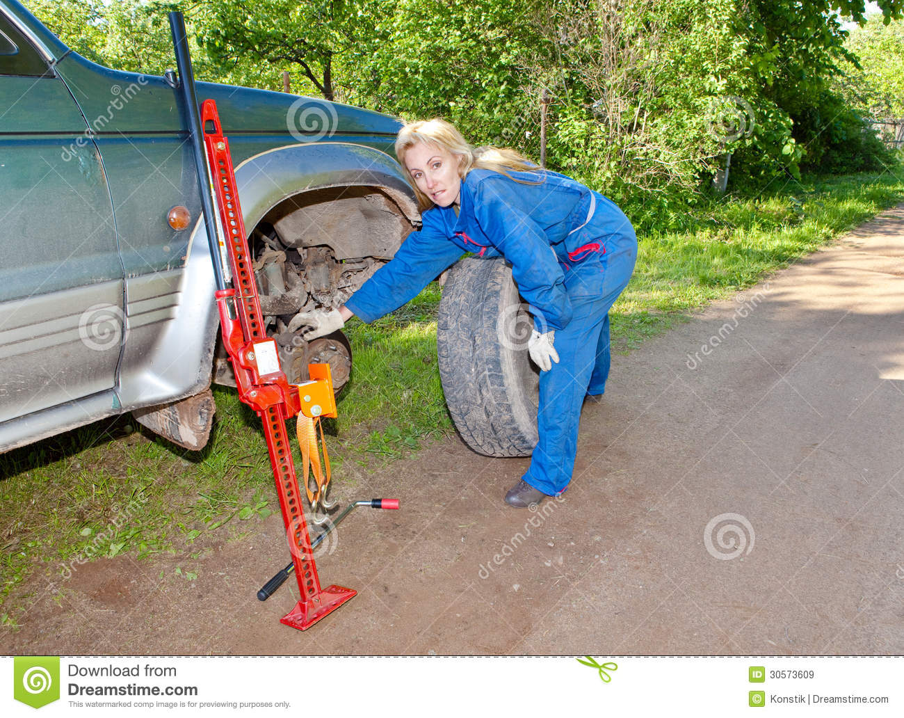 the person in blue working overalls works with a red rack jack about the car stock image image automotive service manuals automobile service manuals online