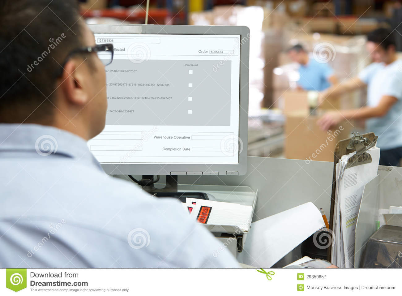 Person At Computer Terminal In Distribution Warehouse