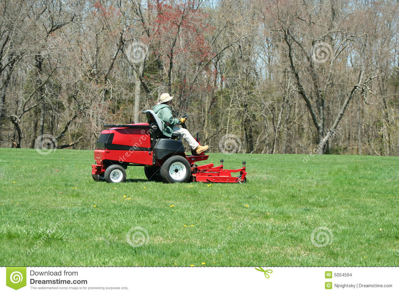 Person cutting the lawn on a riding mower stock photo for Lawn mower cutting grass
