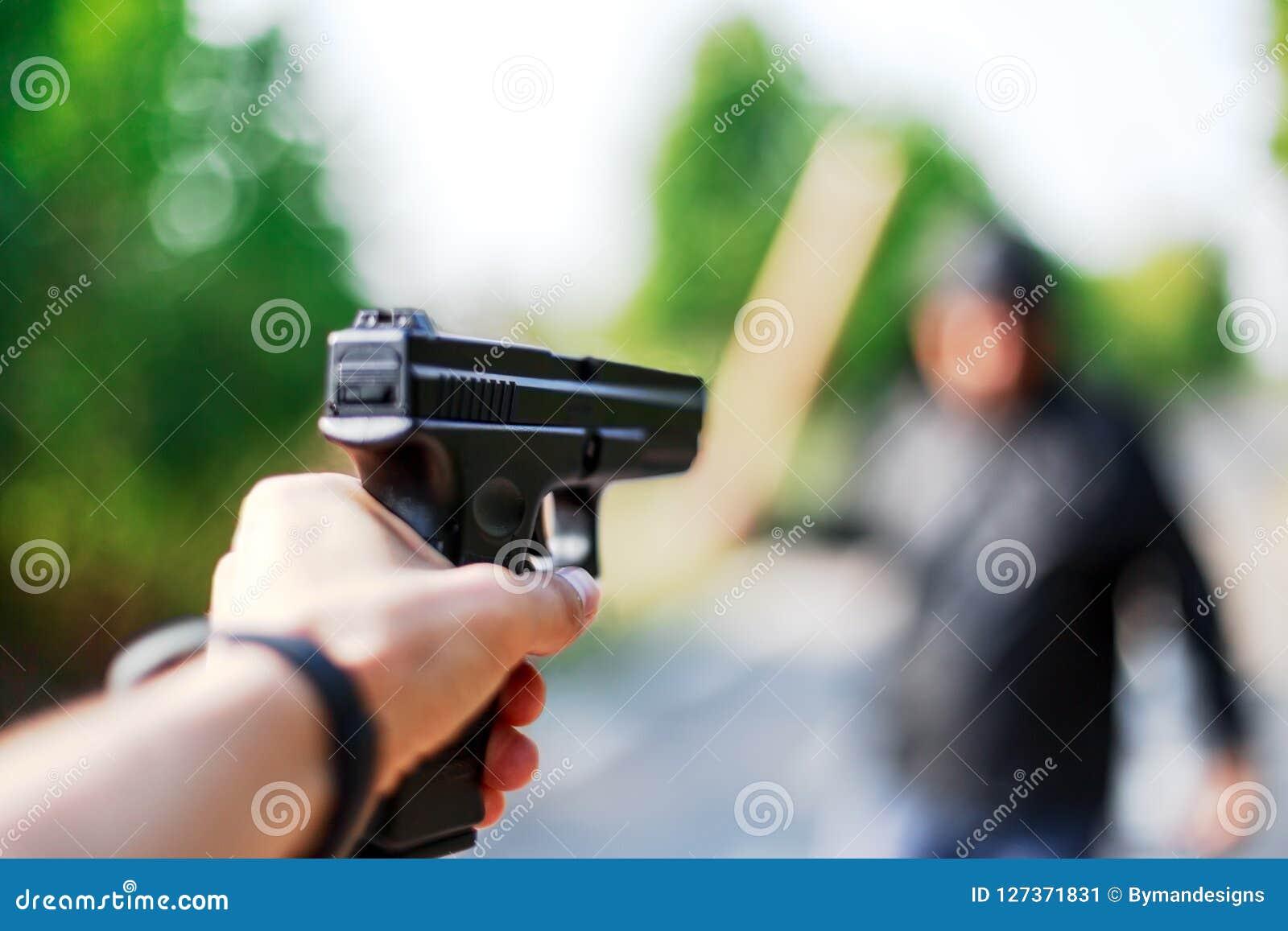 Person, die ein Gewehr auf den Angreifer zeigt