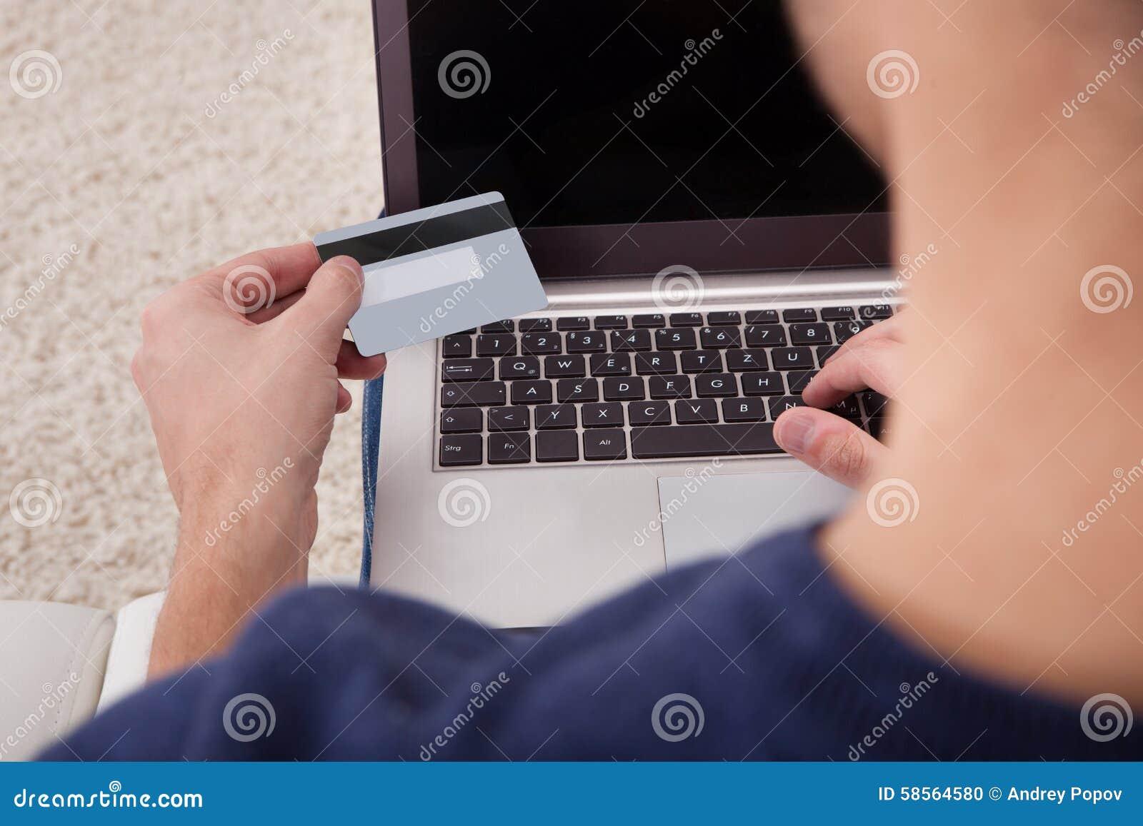 Person, die Kreditkarte unter Verwendung des Laptops hält